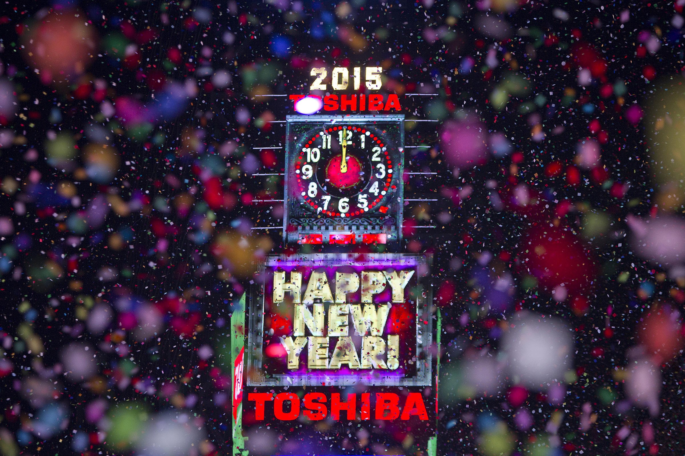 Confetti flies around the ball and countdown clock in Times Square on New Year's Eve in New York January 1, 2015. REUTERS/Carlo Allegri (UNITED STATES - Tags: SOCIETY ANNIVERSARY) - RTR4JSGR
